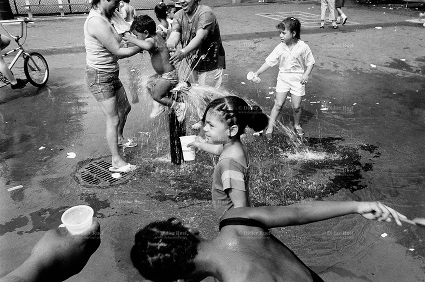 USA. New York City. Spanish Harlem. Public park. Chichi (C) and her friends play at the water fountain in the summer time. Mothers and children. Chichi and her Puerto Rican family lives below the poverty line and receives public assistance (AFDC, Home Relief, Supplemental Security Income and Medicaid). Spanish Harlem, also known as El Barrio and East Harlem, is a low income neighborhood in Harlem area. Spanish Harlem is one of the largest predominantly Latino communities in New York City. 28.06.88 © 1988 Didier Ruef .