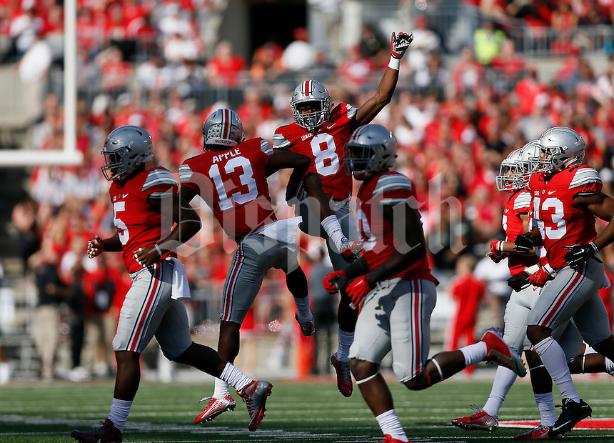 Ohio State Buckeyes cornerback Gareon Conley (8) is congratulated by cornerback Eli Apple (13) after an interception during the first quarter of the NCAA football game against the Hawaii Warriors at Ohio Stadium in Columbus on Sept. 12, 2015. (Adam Cairns / The Columbus Dispatch)