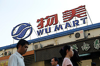 People pass by Wu Mart supermarket, Beijing, China. Wu Mart, the Beijing-based chain, was founded in the early 1990s by Zhang Wenzhong. Its name smacks of the fame of U.S. retail giant Wal-Mart. Wu Mart and Wal-Mart are competing in different arenas and each appears to be going after a different class of consumer. By 2005, Wumart had more than 450 hypermarkets, supermarkets and convenience stores, and is one of only a few Chinese retailers whose shares are publicly traded..02 Jun 2011