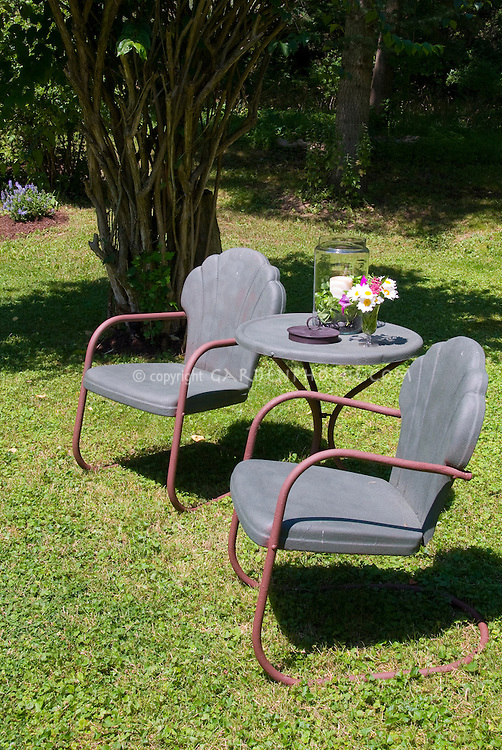 50s metal vintage chairs and table being used in the garden for charming style