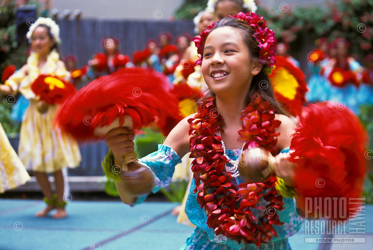 Young hula dancers with feathered uli uli (gourd rattles), Lei Day celebration at Hilton Hawaiian Village Hotel