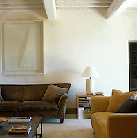 The main living space was formerly a hay store with a rough dirt floor that was replaced with untreated travertine.  The white artwork over the sofa is by Enrico Castellani