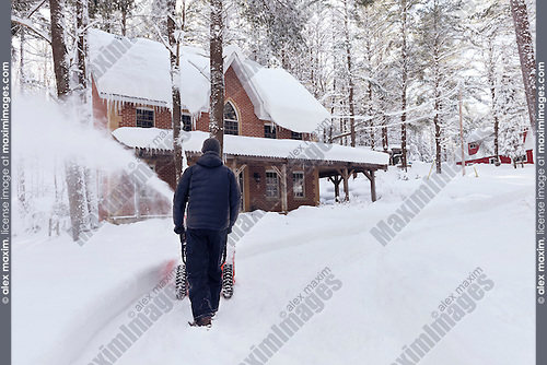 Man with a snow blower clearing a driveway by a house in a beautiful snowy winter scenery of Muskoka, Ontario, Canada