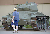 Viistors walk by a M24, U.S. Light Tank used for scouting and reconnaissance in the late days of WWII.  Two Cadillac V-6 engines powered this 19 ton and its crew of four up to 35 mph on display fronting the U.S. Army Museum located in Waikiki, Honolulu, Hawaii on December 28, 2012. .Credit: Cory Lum / Pool via CNP