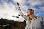 San Francisco Garter Snake (Thamnophis sirtalis tetrataenia) researcher Michelle Thompson weighing snake, Pescadero, California