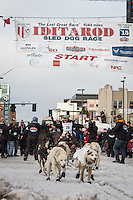 Scott Janssen and team leave the ceremonial start line with an Iditarider at 4th Avenue and D street in downtown Anchorage, Alaska during the 2015 Iditarod race. Photo by Jim Kohl/IditarodPhotos.com