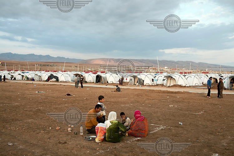 A family who arrived from Syria the day before wait to recieve some shelter at Domiz refugee camp. 81,000 Kurds from Syria have fled the civil war in their home country and taken refuge in northern Iraq. .