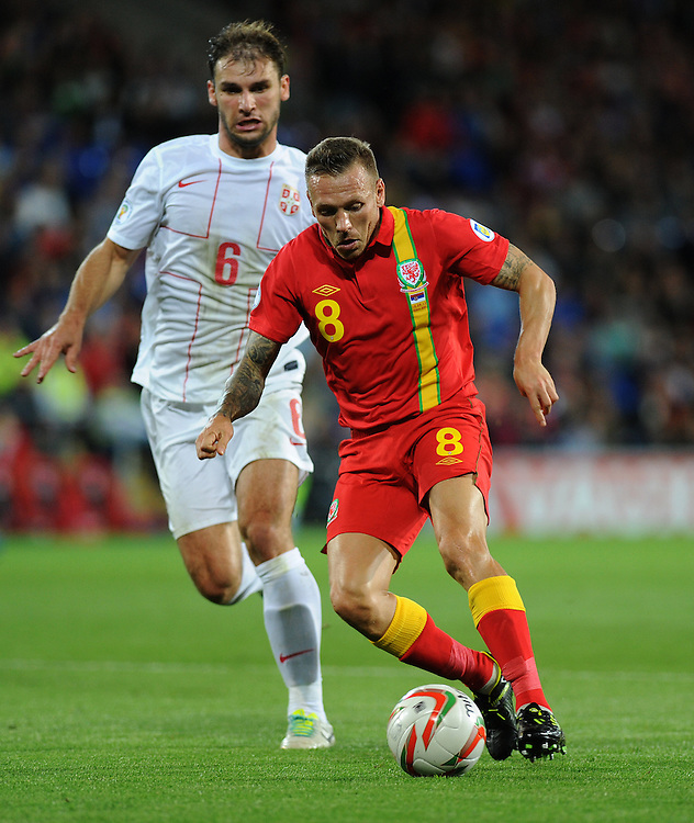 Serbia's Branslav Ivanovic vies for possession with Wales Craig Bellamy<br /> <br /> (Photo by Ashley Crowden/CameraSport)<br /> <br /> Football - FIFA 2014 World Cup Qualifying Match - Wales v Serbia - Tuesday 10th September 2013 - Cardiff City Stadium - Cardiff <br /> <br /> &copy; CameraSport - 43 Linden Ave. Countesthorpe. Leicester. England. LE8 5PG - Tel: +44 (0) 116 277 4147 - admin@camerasport.com - www.camerasport.com