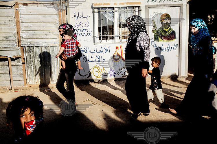 A group of women and children walk past a portacabin with a mural of an armed man on its door. Approximately two million people have fled the conflict in Syria. At least 130,000 of them live in Zaatari Refugee Camp, although it was designed to house 60,000, and a further 2,000 people arrive each day.