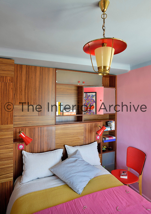 One wall of the bedroom features a built-in cupboard of natural wood, which is illuminated by a vintage pendant light attributed to Pierre Guariche and an artwork by John One is reflected in the mirror behind the bed