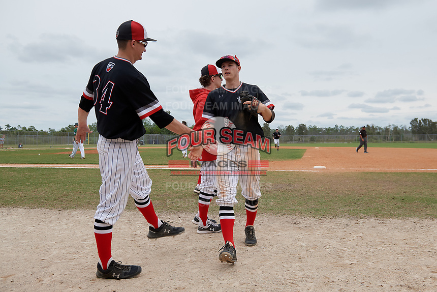 Edgewood Eagles shortstop Ryan Fields (9) is greeted at the dugout by Paul Cappetta (36) during a game against the Babson Beavers on March 18, 2019 at Lee County Player Development Complex in Fort Myers, Florida.  Babson defeated Edgewood 23-7.  (Mike Janes/Four Seam Images)