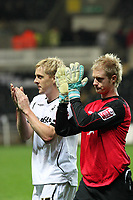 Pictured L-R: Garry Monk captain and Alan Tate of Swansea who substituted injured goalkeeper Dorus de Vries thanks his team's supporters after the final whistle. <br />