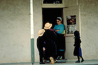 The Amish female teacher waits at the door as elementary school children enter. Amish. Lancaster Pennsylvania United States One room school.