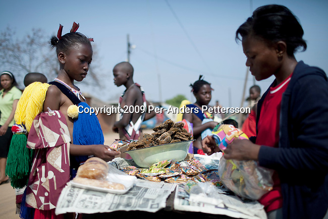 LUDZIDZINI, SWAZILAND - AUGUST 30: An unidentified girl buys dried fish from a trader before a traditional Reed dance ceremony at the Royal Palace on August 30, 2009, in Ludzidzini, Swaziland. About 80.000 virgins from all over the country attended this yearly event, which goes on for a week and which is the biggest in Swazi culture. Many of the girls stayed in tents and slept on the ground. It was founded to celebrate the beauty of Swazi women and girls. King Mswati III, and absolute monarch, was born in 1968 and he has 14 wives and many children. The king danced with his men in front of the 80.000 girls. Many of the girls hope to get noticed by the king and to be chosen as a future wife, a ticket from poverty and into a life of privilege and luxury. The country is one of the poorest in the world and it is struggling with a high prevalence of HIV-Aids and severe poverty. (Photo by: Per-Anders Pettersson)....