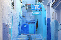 Narrow stepped street painted blue with signs for a hotel and restaurant in the medina or old town of Chefchaouen in the Rif mountains of North West Morocco. Chefchaouen was founded in 1471 by Moulay Ali Ben Moussa Ben Rashid El Alami to house the muslims expelled from Andalusia. It is famous for its blue painted houses, originated by the Jewish community, and is listed by UNESCO under the Intangible Cultural Heritage of Humanity. Picture by Manuel Cohen
