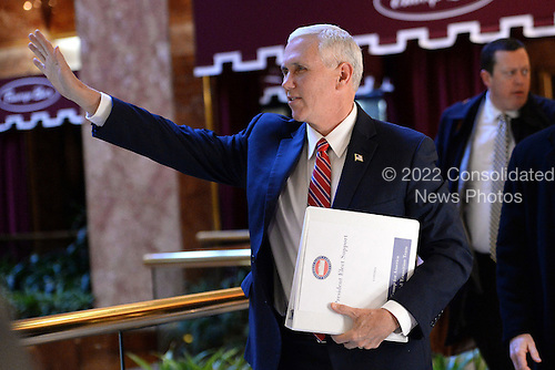 United States Vice President-elect Mike Pence waves to bystanders as he walks through lobby of the Trump Tower in New York, New York, on November 22, 2016.<br /> Credit: Anthony Behar / Pool via CNP
