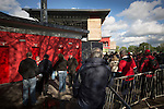 Fans gathering outside a turnstile at Broadhurst Park, Manchester, the new home of FC United of Manchester before the club's match against Benfica, champions of Portugal, which marked the official opening of their new stadium. FC United Manchester were formed in 2005 by fans disillusioned by the takeover of Manchester United by the Glazer family from America. The club gained several promotions and played in National League North in the 2015-16 season, but lost this match 1-0.