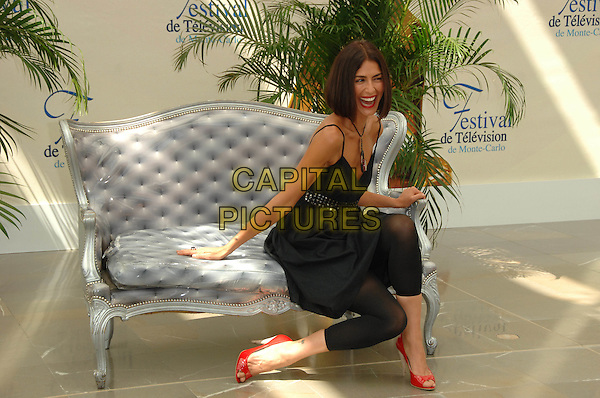 "ELINI TZIMAS.Photocall promoting the television series ""Clarol"" on the third day of the 2008 Monte Carlo Television Festival held at Grimaldi Forum, Monaco, Principality of Monaco..June 10th, 2008.full length black dress leggings orange open toe shoes sitting sofa couch necklace mouth open laughing .CAP/TTL .© TTL/Capital Pictures"