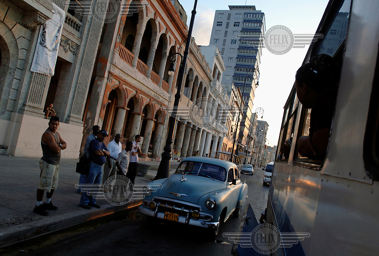 An American vintage car passes people waiting for the bus on the Malecon.