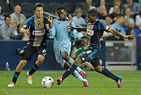 Sporting KC midfielder Peterson Joseph is tackled by Union players Michael Farfan (21) and Raymon Gaddis (28).Sporting Kansas City defeated Philadelphia Union 2-1 at LIVESTRONG Sporting Park, Kansas City, KS.