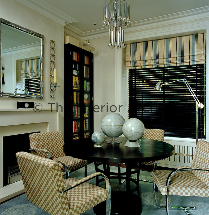 The study is furnished with a round table and a set of Mies van der Rohe chairs covered in checked fabric