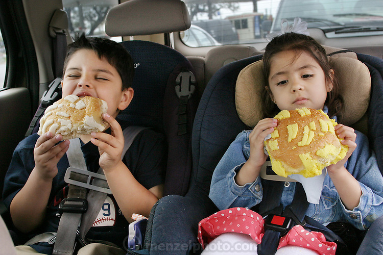 (MODEL RELEASED IMAGE). After going grocery shopping in their local San Antonio, Texas supermarket, Brian and Brianna Fernandez devour Texas-size pan dulces in the back of the family minivan. (Supporting image from the project Hungry Planet: What the World Eats.)