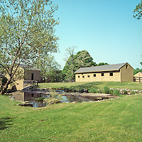 View over an ornamental lake to the stables and mill barn