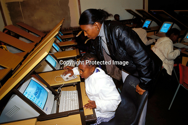 dicompu00039 SOWETO, SOUTH AFRICA - JULY 12: An unidentified child is instructed by her teacher during a computer class on July 12, 2002 at a Catholic school in Soweto, a black township outside Johannesburg, South Africa. Soweto is the largest township in the country and itÕs estimated that about 3-4 million people resides there..(Photo: Per-Anders Pettersson /iAfrika Photos)...