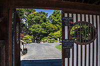 "The sign says, ""Welcome to the Japanese Garden"" and the gate opens into a quiet space of green, manicured plants and a large pond filled with colorful koi fish."
