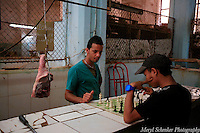 Two men play chess on the meat counter in Old Havana, Cuba -Photo by Meryl Schenker