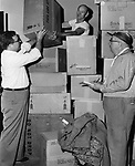 After the August flood, 1,600 pounds of clothing were received by the Waterbury Lodge of Elks from the Sturgis, Mich. Lodge, with a message of sympathy for the great flood loss. This photograph shows clothing being classified by Daniel O'Connor, left rear, handing a box to Attorney James F. McGrath exalted ruler, while James J. Donahue, club steward, right marks the notation.