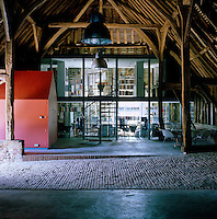 The sleek, 21st-century stand alone, two-storey glass and steel design studio contrasts with the rustic wooden structure of the vast 14th-century cathedral barn within which it has been built