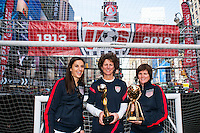 U.S. women national team midfielder Carli Lloyd poses for a photo with former women's national team players Michelle Akers and April Heinrichs during the centennial celebration of U. S. Soccer at Times Square in New York, NY, on April 04, 2013.