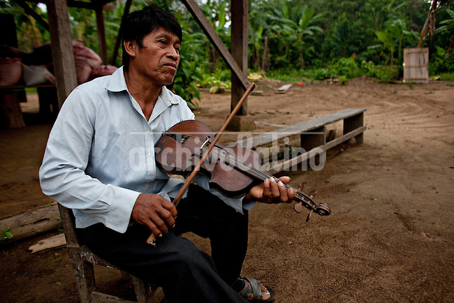 Indigenous Mojeno representative Santiago Tamo Noza plays violin in  San Miguelito del Isiboro, in the hearth of TIPNIS reserve, Bolivia.The government has decided to build a road through the national reserve , sparking the protests of indian comunities backed by environmentalist stating that  TIPNIS will lose part of his rich fauna and flora. It is considered one of the few remaining natural areas in the Bolivian amazon that is yet respected by man.
