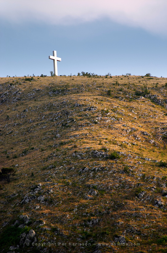 A cross on a hilltop near the city. Historic town of Mostar. Federation Bosne i Hercegovine. Bosnia Herzegovina, Europe.