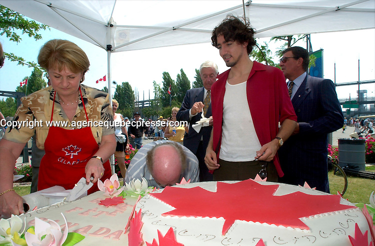 July 1 2002, Montreal, Quebec, Canada<br /> <br /> Lucienne Robillard, President Treasury Board of canada (L), get help from<br /> Justin Trudeau, Former Canada Prime Minister Pierrre E TRudeau's son (R) to cut a giant cake distributed to people attending the Canada day celebrations,  July 1st 2001, in the Old-Port of Montreal. <br /> <br /> Mandatory Credit: Photo by Pierre Roussel- Images Distribution. (&copy;) Copyright 2002 by Pierre Roussel