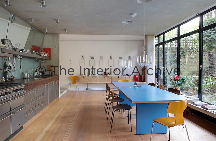 Modern spacious kitchen with stainless steel units and blue table in centre