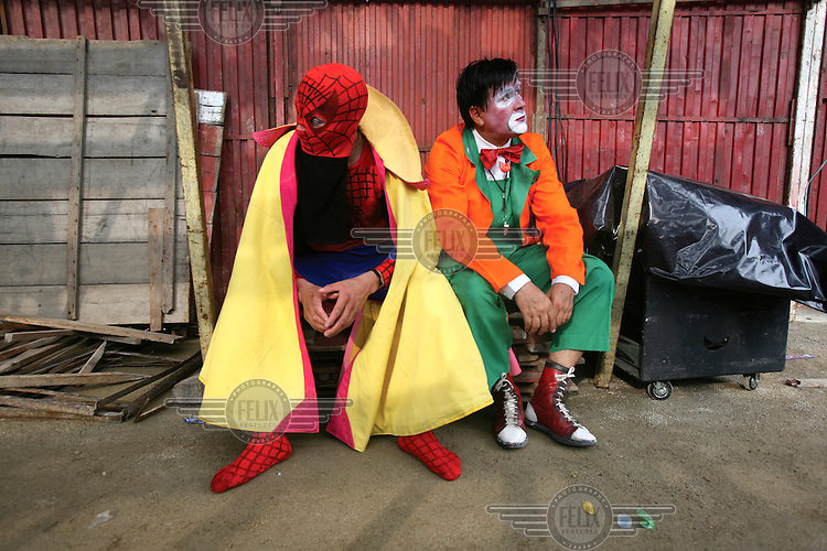 Jamie Vizcaino, right, a bullfighting clown, waits underneath the seats of a bullring to perform in Tena.