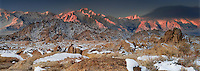 02000024 panoramic winter sunrise with snow covered granite boulders in the bureau of land management protected land the alabama hills in the southern section of the eastern sierras with lone pine peak and mount whitneyl in the background in kern county california