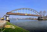 NIEUWEGEIN - In Nieuwegein ligt de oude Overeindsebrug over het Lekkanaal klaar om in het weekend van plaats te wisselen met de nieuwe stalen boogbrug die verderop langs het Amsterdam-Rijnkanaal klaar ligt. De door bouwcombinatie KWS Mercon gebouwde brug is de afgelopen dagen vanaf de werf in Gorinchem per ponton vervoerd naar Nieuwegein en zal in opdracht van Rijkswaterstaat met drijvende kranen worden ingevaren. De renovatie van de Overeindsebrug is onderdeel van het project KARGO (Kunstwerken Amsterdam-Rijnkanaal Groot Onderhoud) waarbij Rijkswaterstaat acht stalen bruggen vernieuwd. COPYRIGHT TON BORSBOOM