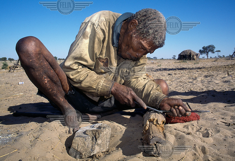 A San Bushman works on a metal implement at the Xade settlement before the entire San population were removed, between 1997 and 2002, to a new location outside the Central Kalahari Game Reserve.