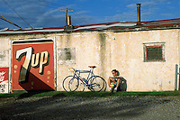 Warm tone image of a cyclist resting against a wall with his bicycle, next to a 7 Up advertising sign.