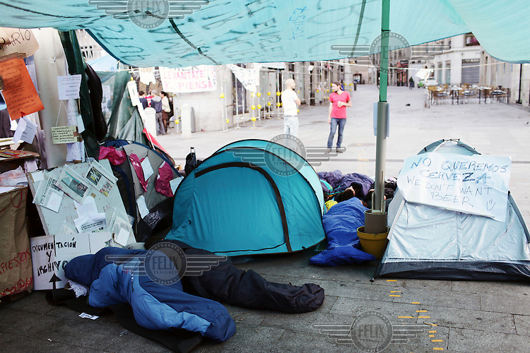 People sleep among tents pitched by the self-named 'indignados' who are protesting against cuts, austerity and joblessness. A sign stuck to one of the tents reads, 'We don't want a beer'. In May 2012, following a worsening financial crisis and a deepening recession in Spain, thousands of people started to gather in Spanish cities to protest against austerity, the global financial system, high unemplyment rate (Spain's is the highest rate in Europe) and the lack of opportunities. The protest movement has become known as 'los indignados' (the indignant ones).