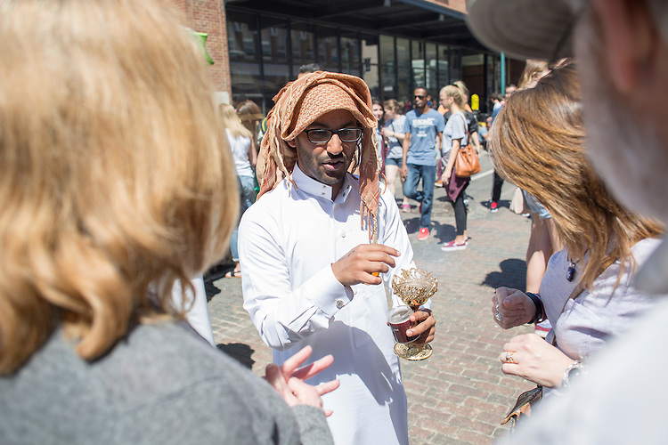 Hasan Alghamdi, a second year graduate student, shares bakore, which is similar to incense in Saudi Arabia, with others at the International Street Fair on April 16, 2016.