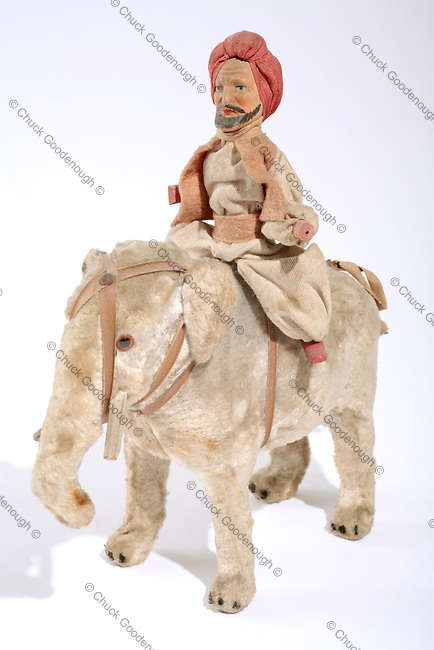 Photo of an old toy Elephant with a rider wearing a turban.