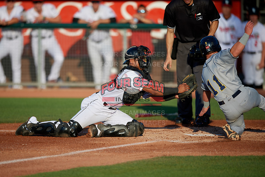 Lansing Lugnuts catcher Gabriel Moreno (23) tags Morgan McCullough (11) out at home during a Midwest League game against the Burlington Bees on July 18, 2019 at Cooley Law School Stadium in Lansing, Michigan.  Lansing defeated Burlington 5-4.  (Mike Janes/Four Seam Images)