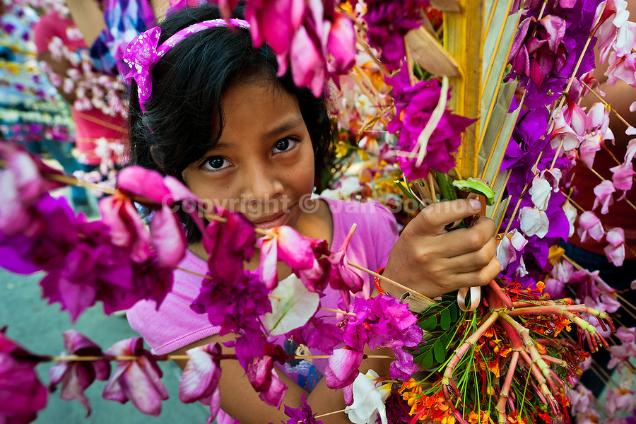 "A Salvadoran girl carries a palm branch with colorful flower blooms during the procession of the Flower & Palm Festival in Panchimalco, El Salvador, 8 May 2011. On the first Sunday of May, the small town of Panchimalco, lying close to San Salvador, celebrates its two patron saints with a spectacular festivity, known as ""Fiesta de las Flores y Palmas"". The origin of this event comes from pre-Columbian Maya culture and used to commemorate the start of the rainy season. Women strip the palm branches and skewer flower blooms on them to create large colorful decoration. In the afternoon procession, lead by a male dance group performing a religious dance-drama inspired by the Spanish Reconquest, large altars adorned with flowers are slowly carried by women, dressed in typical costumes, through the steep streets of the town."