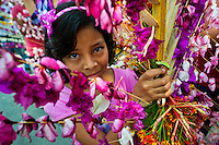 """A Salvadoran girl carries a palm branch with colorful flower blooms during the procession of the Flower & Palm Festival in Panchimalco, El Salvador, 8 May 2011. On the first Sunday of May, the small town of Panchimalco, lying close to San Salvador, celebrates its two patron saints with a spectacular festivity, known as """"Fiesta de las Flores y Palmas"""". The origin of this event comes from pre-Columbian Maya culture and used to commemorate the start of the rainy season. Women strip the palm branches and skewer flower blooms on them to create large colorful decoration. In the afternoon procession, lead by a male dance group performing a religious dance-drama inspired by the Spanish Reconquest, large altars adorned with flowers are slowly carried by women, dressed in typical costumes, through the steep streets of the town."""