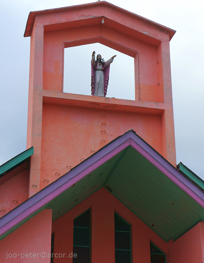 pink church dedicated to virgin Mary half way coastal city Ende to mountain village Moni, island  Flores in archipelago of Indonesia