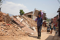 A man saves his belongings from his collapsed home at Changu village,  Bhaktapur, outside of Kathmandu, Nepal. May 05, 2015